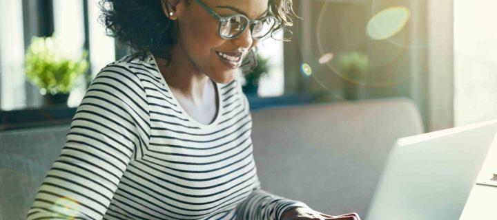 Black woman typing on a laptop