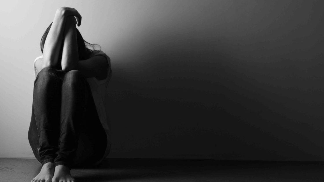 teen girl sitting alone on the floor in a dark room
